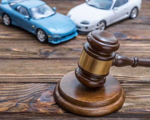 a gavel on a table with two toy cars crashing