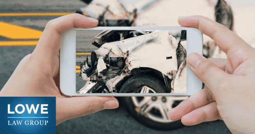 person taking picture of damage to a vehicle after a car accident