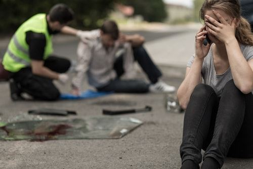 Woman on the phone sitting at an accident scene